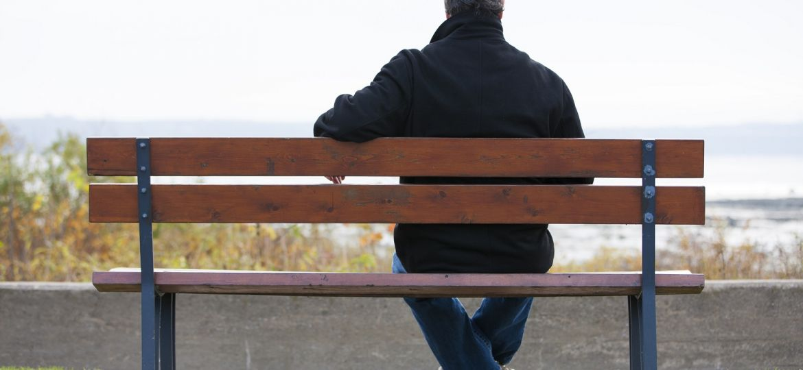 Mature man sitting on park bench overlooking river.